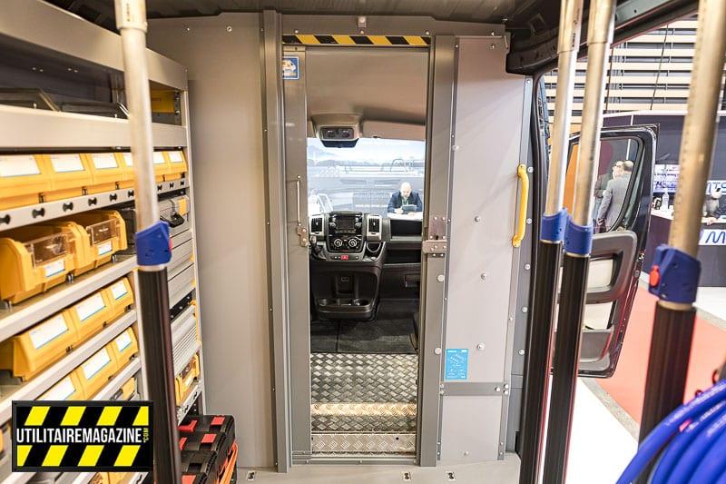 Une porte sécurisée entre la cabine et la benne du Ducato. On voit aussi les bras télescopique pour l'arrimage sécurisé des objets transportés.