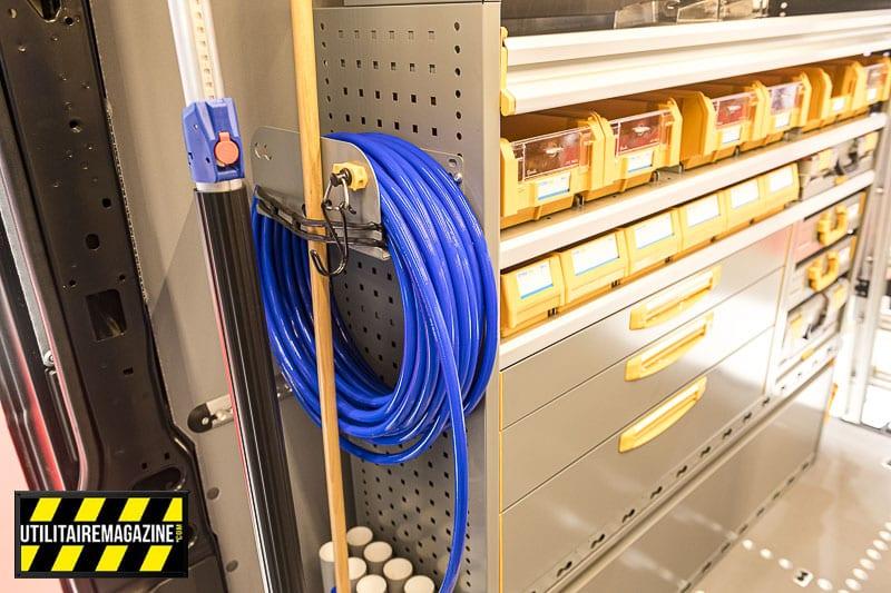 Les grilles latérales des meubles sont perforées et peuvent recevoir de nombreux accessoires, ici un porte tuyau / porte outils.